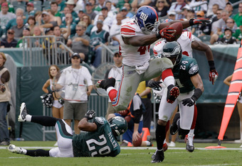 PHILADELPHIA, PA - SEPTEMBER 25: Running back  Ahmad Bradshaw #44 of the New York Giants jumps over defenders Nate Allen #29 and Nnamdi Asomugha #24 of the Philadelphia Eagles for a touchdown in the fourth quarter at Lincoln Financial Field on September 2
