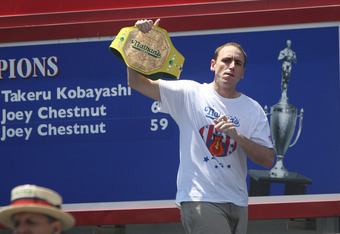 NEW YORK - JULY 4: Joey Chestnut of San Jose, California walks on stage holding his old champion belt as the Nathan's Famous Fourth of July hot dog eating contest begins on July 4, 2009 in Coney Island in the Brooklyn borough of New York City. Chestnut de