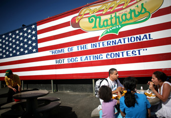 NEW YORK - JULY 4: A family eats hot dogs in front of an advertisement for the Nathan's Famous Fourth of July hot dog eating contest, to undergo later that day, on July 4, 2009 in Coney Island in the Brooklyn borough of New York City. Joey Chestnut of San
