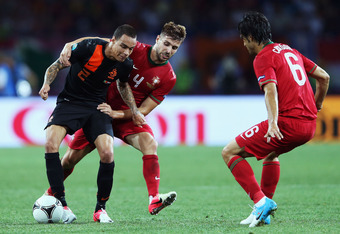 KHARKOV, UKRAINE - JUNE 17:  Gregory van der Wiel (L) of Netherlands battles for the ball with Miguel Veloso of Portugal during the UEFA EURO 2012 group B match between Portugal and Netherlands at Metalist Stadium on June 17, 2012 in Kharkov, Ukraine.  (P