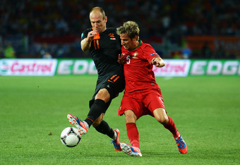 KHARKOV, UKRAINE - JUNE 17:  Arjen Robben of Netherlands battles for the ball with Fabio Coentrao of Portugal during the UEFA EURO 2012 group B match between Portugal and Netherlands at Metalist Stadium on June 17, 2012 in Kharkov, Ukraine.  (Photo by Lar