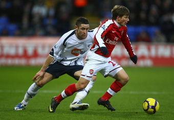 BOLTON, ENGLAND - JANUARY 17:  Andrey Arshavin of Arsenal is pressurised by Gary Cahill of Bolton Wanderers during the Barclays Premier League match between Bolton Wanderers and Arsenal at the Reebok Stadium on January 17, 2010 in Bolton, England. (Photo by Alex Livesey/Getty Images)