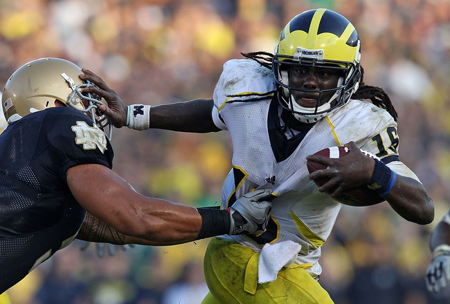 SOUTH BEND, IN - SEPTEMBER 11: Denard Robinson #16 of the Michigan Wolverines pushes off a tackle attempt by Manti Te'o #5 of the Notre Dame Fighting Irish in the final minute at Notre Dame Stadium on September 11, 2010 in South Bend, Indiana. Michigan defeated Notre Dame 28-24. (Photo by Jonathan Daniel/Getty Images)