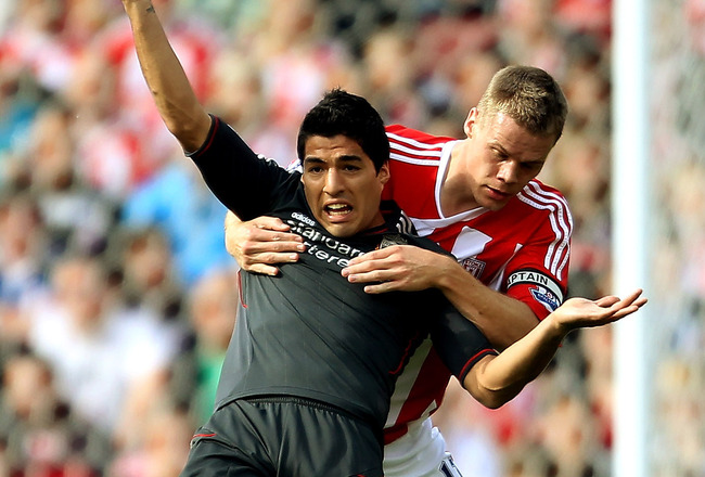 STOKE ON TRENT, ENGLAND - SEPTEMBER 10:  Luis Suarez of Liverpool (L) holds off Ryan Shawcross of Stoke during the Barclays Premier League match between Stoke City and Liverpool at Britannia Stadium on September 10, 2011 in Stoke on Trent, England.  (Photo by Scott Heavey/Getty Images)