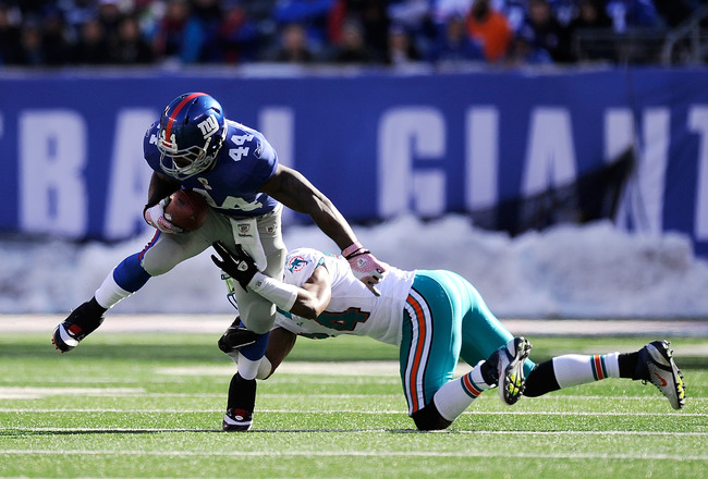 EAST RUTHERFORD, NJ - OCTOBER 30:  Ahmad Bradshaw #44 of the New York Giants breaks the tackle of Sean Smith #24 of the Miami Dolphins during the second quarter at MetLife Stadium on October 30, 2011 in East Rutherford, New Jersey.  (Photo by Patrick McDermott/Getty Images)
