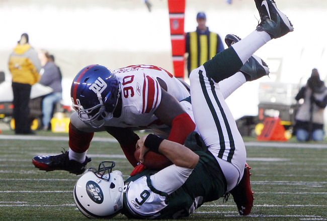 EAST RUTHERFORD, NJ - DECEMBER 24:  Mark Sanchez #6 of the New York Jets is sacked by Jason Pierre-Paul #90 of the New York Giants during the second quarter during a game at MetLife Stadium on December 24, 2011 in East Rutherford. New Jersey. (Photo by Rich Schultz /Getty Images)