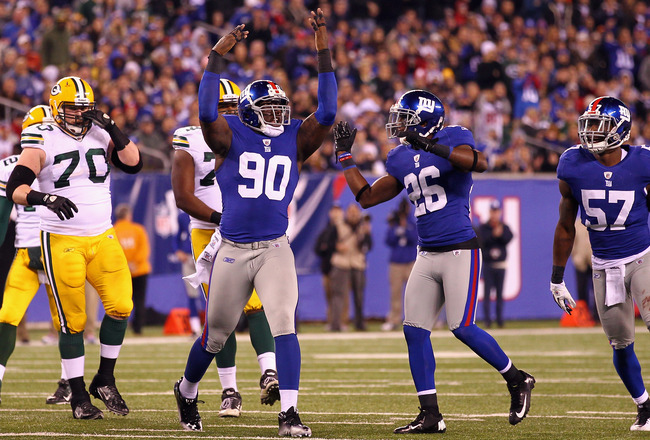 EAST RUTHERFORD, NJ - DECEMBER 04:  Jason Pierre-Paul #90, Antrel Rolle #26 and Jacquian Williams #57 of the New York Giants react after a defensive stop against the Green Bay Packers at MetLife Stadium on December 4, 2011 in East Rutherford, New Jersey.  (Photo by Al Bello/Getty Images)