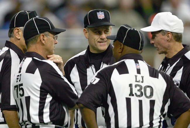 DETROIT - SEPTEMBER 16:  Umpire Richard Hall#49 talks with line judges Darryll Lewis #130. Bill Leavy#127 and field judge Rob Vernatchi(75) during the game between the Minnesota Vikings and the Detroit Lions at Ford Field on September 16, 2006 in Detroit, Michigan.  (Photo by Harry How/Getty Images)