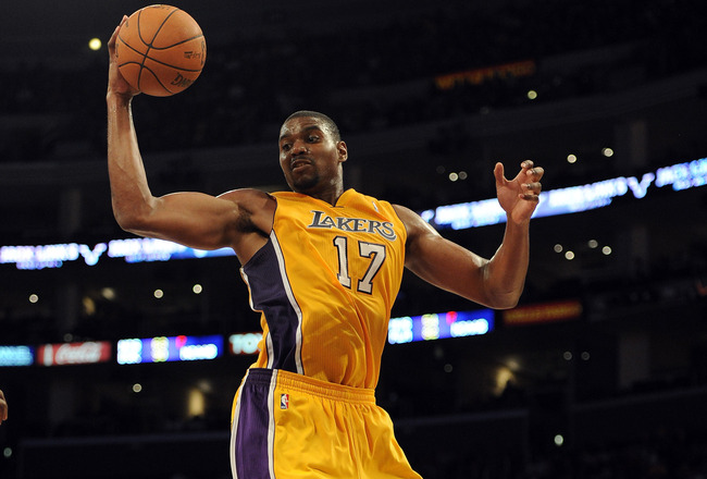 LOS ANGELES, CA - DECEMBER 19:  Andrew Bynum #17 of the Los Angeles Lakers grabs a rebound during the game against the Los Angeles Clippers at Staples Center on December 19, 2011 in Los Angeles, California. NOTE TO USER: User expressly acknowledges and agrees that, by downloading and/or using this Photograph, user is consenting to the terms and conditions of the Getty Images License Agreement. Mandatory Copyright Notice: Copyright 2011 NBAE  (Photo by Harry How/Getty Images)