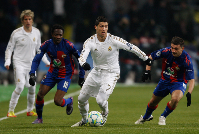 MOSCOW, RUSSIA - FEBRUARY 21: Cristiano Ronaldo (C) of Real Madrid runs with the ball past Ahmed Musaab (2nd L) and Alan Dzagoev (R) of CSKA Moskva during the UEFA Champions League round of 16, first leg match between CSKA Moscow and Real Madrid at the Luzhniki Stadium on February 21, 2012 in Moscow, Russia.  (Photo by Harry Engels/Getty Images)