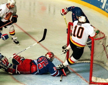 11 Jun 1994: PAVEL BURE HANGS ON THE CROSS BAR TO AVOID DIVING RANGERS GOALTENDER MIKE RICHTER DURING THE FIRST PERIOD OF GAME SIX OF THE STANLEY CUP FINALS IN VANCOUVER, BRITISH COLUMBIA.
