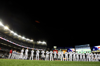 NEW YORK - OCTOBER 18:  The New York Yankees and the Texas Rangers line up on the foul lines during the performance of the National Anthem prior to playing Game Three of the ALCS during the 2010 MLB Playoffs at Yankee Stadium on October 18, 2010 in New Yo
