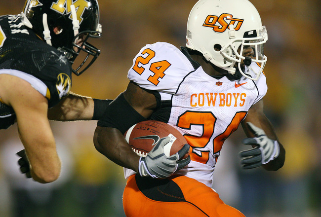 COLUMBIA, MO - OCTOBER 11:  Kendall Hunter #24 of the Oklahoma State Cowboys drags a defender of the Missouri Tigers for yardage on October 11, 2008 at Memorial Stadium in Columbia, Missouri.  (Photo by G. Newman Lowrance/Getty Images)