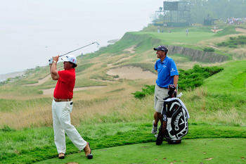 KOHLER, WI - AUGUST 10:  Phil Mickelson (L) hits a shot while caddie Jim 'Bones' Mackay looks on during a practice round prior to the start of the 92nd PGA Championship on the Straits Course at Whistling Straits on August 10, 2010 in Kohler, Wisconsin.  (
