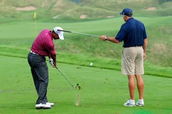 KOHLER, WI - AUGUST 10:  Tiger Woods works on his golf swing with his caddie Steve Williams (R) during a practice round prior to the start of the 92nd PGA Championship on the Straits Course at Whistling Straits on August 10, 2010 in Kohler, Wisconsin.  (P