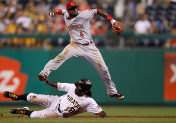 PITTSBURGH - AUGUST 03:  Brandon Phillips #4 of the Cincinnati Reds attempts to turn the double play over Lastings Milledge #85 of the Pittsburgh Pirates during the game on August 3, 2010 at PNC Park in Pittsburgh, Pennsylvania.  (Photo by Jared Wickerham