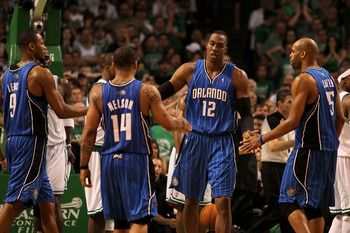 BOSTON - MAY 24:  Dwight Howard #12 of the Orlando Magic celebrates with Rashard Lewis #9, Jameer Nelson #14 and Vince Carter #15 after he made a basket in overtime the Boston Celtics in Game Four of the Eastern Conference Finals during the 2010 NBA Playo