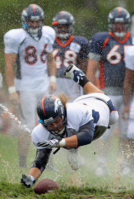 ENGLEWOOD, CO - AUGUST 05:  Offensive lineman Eric Olsen #69 of the Denver Broncos dives for the ball as rookies partake in the slip and slide fumble drill during training camp at Dove Valley on August 5, 2010 in Englewood, Colorado.  (Photo by Doug Pensi