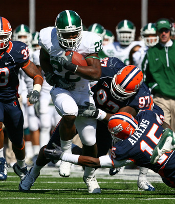 CHAMPAIGN, IL - OCTOBER 10: Larry Caper #22 of the Michigan State Spartans runs past Walter Aikens #15 and Clay Nurse #97 of the Illinois Fighting Illini on October 10, 2009 at Memorial Stadium at the University of Illinois in Champaign, Illinois. (Photo