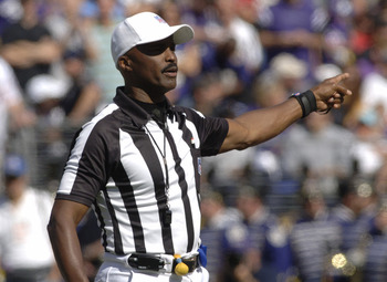 NFL referee Mike Carey calls a penalty at  M&T Bank Stadium as the  Baltimore Ravens host the San Diego Chargers on October 1, 2006 in Baltimore, Maryland.  The Ravens won 16 - 13.  (Photo by Al Messerschmidt/Getty Images)