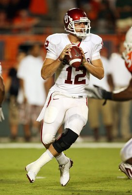 MIAMI GARDENS, FL - OCTOBER 03:  Quarterback Landry Jones #12 of the Oklahoma Sooners drops back to pass against the Miami Hurricanes at Land Shark Stadium on October 3, 2009 in Miami Gardens, Florida. Miami defeated Oklahoma 21-20.  (Photo by Doug Benc/G