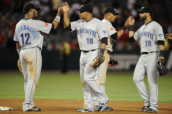 ANAHEIM, CA - AUGUST 13:  Vernon Wells #10, Edwin Encarnacion #12 Jose Bautista and Yunel Escobar #5 of the Toronto Blue Jays celebrate a 3-0 win over the Los Angeles Angels at Angel Stadium on August 13, 2010 in Anaheim, California.  (Photo by Harry How/