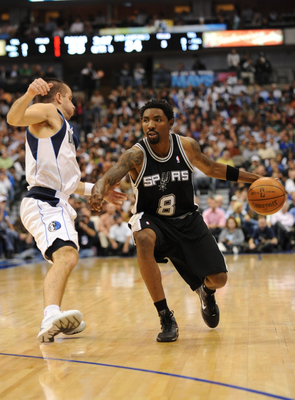 DALLAS - NOVEMBER 18:  Roger Mason Jr. #8 of the San Antonio Spurs moves the ball against Jose Barea #11 of the Dallas Mavericks during the game at American Airlines Center on November 18, 2009 in Dallas, Texas. NOTE TO USER: User expressly acknowledges a