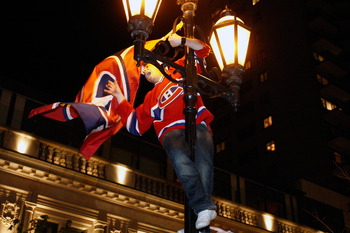 MONTREAL- MAY 12:   A fan hangs a Montreal Canadiens flag from a light post in downtown Montreal after the Montreal Canadiens defeated the Pittsburgh Penguins in Game Seven of the Eastern Conference Semifinals during the 2010 NHL Stanley Cup Playoffs at t