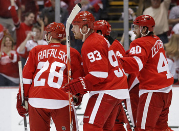 DETROIT - MAY 06:  Johan Franzen #93 of the Detroit Red Wings celebrates with Brian Rafalski #28 and Henrik Zetterberg #40 after his third period and fourth goal of the game while playing the San Jose Sharks in Game Four of the Western Conference Semifina