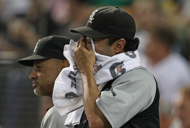 CHICAGO - AUGUST 10: Manager Ozzie Guillen #13 of the Chicago White Sox (R) wipes his face as bench coach Joey Cora watches a game against the Minnesota Twins at U.S. Cellular Field on August 10, 2010 in Chicago, Illinois. The Twins defeated the White Sox