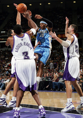 SACRAMENTO, CA - NOVEMBER 11:  Carmelo Anthony #15 of the Denver Nuggets passes over Shareef Abdur-Rahim #3 and Brad Miller #52 of the Sacramento Kings during an NBA game at Arco Arena on November 11, 2005 in Sacramento, California.  NOTE TO USER: User ex