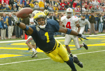 ANN ARBOR, MI - NOVEMBER 22: Braylon Edwards #1 of the Michigan Wolverines dives for a pass from John Navarre as Will Allen #4 of the Ohio State Buckeyes watches behind him during the 100th meeting of the two teams November 22, 2003 at Michigan Stadium in