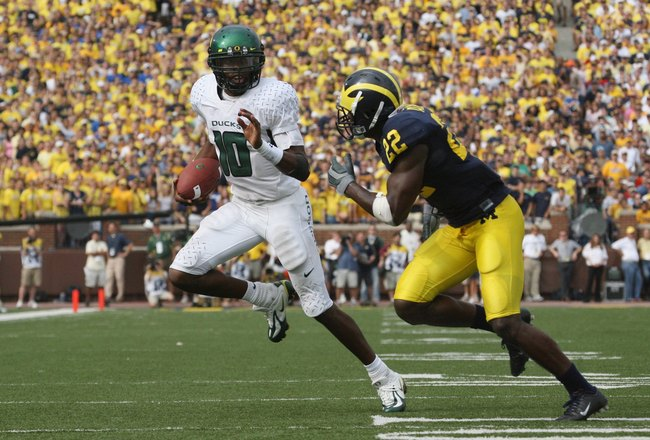 ANN ARBOR, MI - SEPTEMBER 08:  Dennis Dixon #10 of the Oregon Ducks scrambles as he is pressured by Doug Rogan #22 of the Michigan Wolverines during their game on September 8, 2007 at Michigan Stadium in Ann Arbor, Michigan.  The Ducks defeated the Wolver