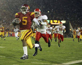 LOS ANGELES, CA - NOVEMBER 19:  Reggie Bush #5 of the USC Trojans carries the ball past Matt Davis #26 of the Fresno State Bulldogs during the game at the Los Angeles Memorial Coliseum on November 19, 2005 in Los Angeles, California. The Trojans won 50-42