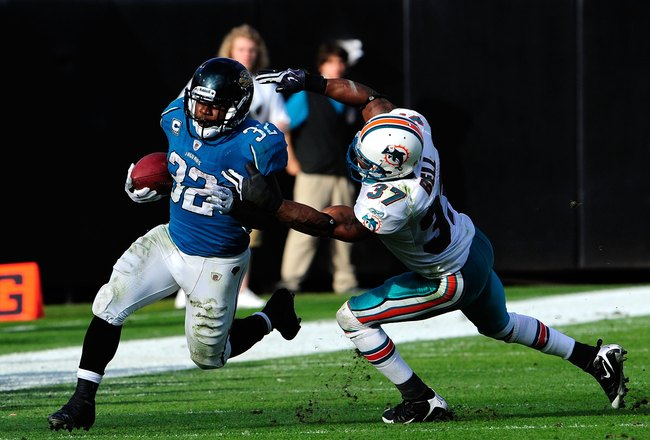 JACKSONVILLE, FL - DECEMBER 13:  Yeremiah Bell #37 of the Miami Dolphins attempts to tackle Maurice Jones-Drew #32 of the Jacksonville Jaguars during the game at Jacksonville Municipal Stadium on December 13, 2009 in Jacksonville, Florida.  (Photo by Sam