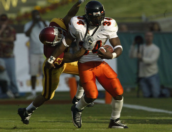 LOS ANGELES - DECEMBER 6:  Running back Steven Jackson #34 of the Oregon State Beavers carries the ball as defensive back Ronald Nunn #23 of the USC Trojans tackles him on December 6, 2003 at the Los Angeles Coliseum in Los Angeles, California.  (Photo by