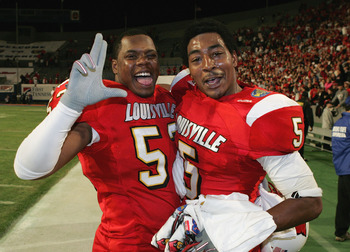 MEMPHIS, TN - DECEMBER 31: Linebacker Jonathan Jackerson #52 and cornerback Antoine Sharp #5 of the Louisville Cardinals celebrate after defeating the Boise State Broncos 44-40 in the AutoZone Liberty bowl at the Liberty Bowl on December 31, 2004 in Memph