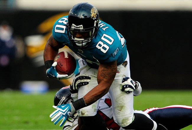 JACKSONVILLE, FL - DECEMBER 06:  Mike Thomas #80 of the Jacksonville Jaguars is tackled by Brice McCain #41 of the Houston Texans during the game at Jacksonville Municipal Stadium on December 6, 2009 in Jacksonville, Florida.  (Photo by Sam Greenwood/Gett