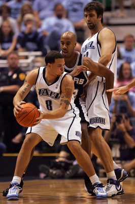 SALT LAKE CITY - MAY 26:  Deron Williams #8 of the Utah Jazz looks to go around Bruce Bowen #12 of the San Antonio Spurs as teammate Mehmet Okur #13 sets a screen in the first quarter of Game Three of the Western Conference Finals during the 2007 NBA Play