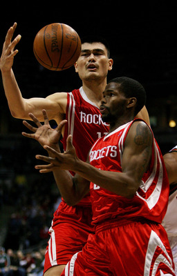 MILWAUKEE - FEBRUARY 09:  Yao Ming #11 and Aaron Brooks #0 of the Houston Rockets try to control the ball during a game against the Milwaukee Bucks on February 9, 2009 at the Bradley Center in Milwaukee, Wisconsin. NOTE TO USER: User expressly acknowledge