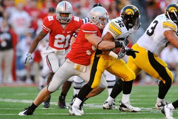 COLUMBUS, OH - NOVEMBER 14:  Linebacker Ross Homan #51 of the Ohio State Buckeyes tackles running back Adam Robinson #32 of the Iowa Hawkeyes at Ohio Stadium on November 14, 2009 in Columbus, Ohio.  (Photo by Jamie Sabau/Getty Images)