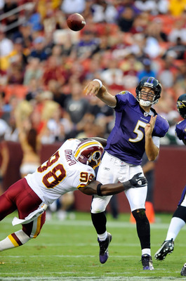LANDOVER, MD - AUGUST 21:  Joe Flacco #5 of the Baltimore Ravens throws a pass during the preseason game as he is hit by Brian Orakpo #98 of the Washington Redskins at FedExField on August 21, 2010 in Landover, Maryland.  (Photo by Greg Fiume/Getty Images