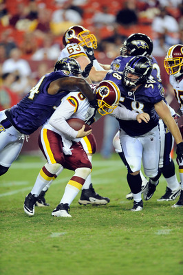 LANDOVER, MD - AUGUST 21:  Rex Grossman #8 of the Washington Redskins is sacked during the preseason game by Jason Phillips #58 and Prescott Burgess #54 of the Baltimore Ravens at FedExField on August 21, 2010 in Landover, Maryland.  (Photo by Greg Fiume/