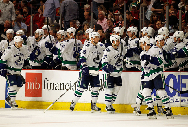 CHICAGO - MAY 01: (L-R) Christian Ehrhoff #5, Shane O'Brien #55, Rick Rypien #37 and Michael Grabner #40 of the Vancouver Canucks are congratulated by teammates after Grabner scored a 2nd period goal against the Chicago Blackhawks in Game One of the Weste