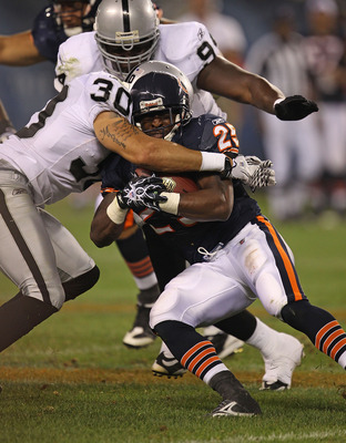 CHICAGO - AUGUST 21: Garrett Wolfe #25 of the Chicago Bears is brought down by Jerome Boyd #30 of the Oakland Raiders during a preseason game at Soldier Field on August 21, 2010 in Chicago, Illinois. The Raiders defeated the Bears 32-17. (Photo by Jonatha