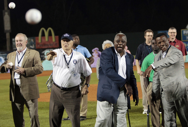 MOBILE, AL - APRIL 14:  Baseball Hall of Famers (L-R) Bruce Sutter, Bob Feller, Hank Aaron and Rickey Henderson throw out the first pitch during pre-game ceremonies following the opening the Hank Aaron Museum at the Hank Aaron Stadium on April 14, 2010 in