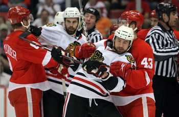 DETROIT - MAY 19:  Adam Burish #37 (2nd R) and Andrew Ladd #16 (2nd L) of the Chicago Blackhawks get tied up with Darren Helm #43 (R) and Justin Abdelkader #8 (L) of the Detroit Red Wings during Game Two of the Western Conference Championship Round of the