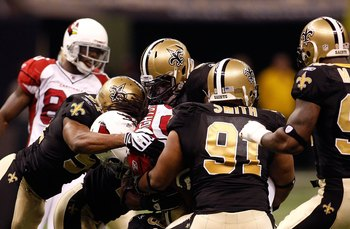 NEW ORLEANS - JANUARY 16:  Jonathan Vilma #51 (L) and Will Smith #91 of the New Orleans Saints with an assits from teammates tackle Tim Hightower #34 of the Arizona Cardinals during the NFC Divisional Playoff Game at Louisana Superdome on January 16, 2010