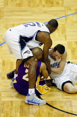 ORLANDO, FL - JUNE 14:  Derek Fisher #2 of the Los Angeles Lakers holds the ball as both Dwight Howard #12 and Hedo Turkoglu #15 of the Orlando Magic go after it in Game Five of the 2009 NBA Finals on June 14, 2009 at Amway Arena in Orlando, Florida.  NOT