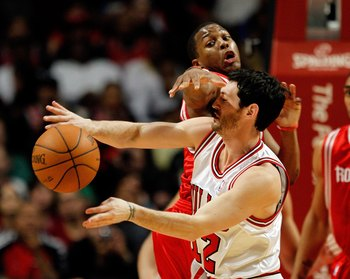 CHICAGO - MARCH 22: Kirk Hinrich #12 of the Chicago Bulls is hit in the face while passing by Kyle Lowry #7 of the Houston Rockets at the United Center on March 22, 2010 in Chicago, Illinois. NOTE TO USER: User expressly acknowledges and agrees that, by d